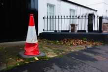 Red And White Traffic No Parking Cone On A Piece Of Cement With Black Doors And Railings In The Background