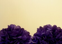 Two Artificial Purple Flowers On A Beige Background. Space For The Text.