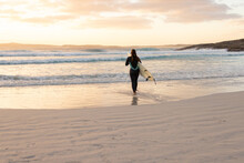 Wide View Of Surfer Heading Into The Surf At Sunset