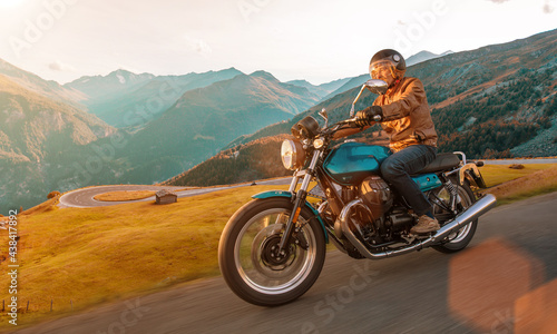 Motorcycle driver riding in Alpine landscape. Lifestyle photo with motion blur effect and copyspace. #438417892