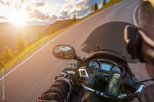 Motorcycle driver riding on mountains highway, handlebars view, Dolomites, central Europe. #438417899