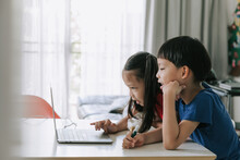 Asian Twins Boy And Girl Helping Each Other To Study On Line At Home During Pandemic.