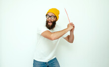 Young Caucasian Hipster Man Holding A Fly Swatter Wanting To Kill Annoying Mosquito Or A Fly.
