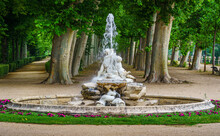Fountain With Water In A Public Park With Large Trees In The Background.