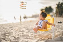 Baby In White Dress Sit On The Chair Beach Yellow Color With Relaxing And The Wind Blows In Evening Time And Beautiful Sunset Light
