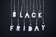 Black Paper Cut Out Tags On Dangling On White Strings With White Letters Spelling Black Friday On Black Background