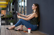 Leinwandbild Motiv Attractive female generation Z dressed in casual wear holding modern touch pad gadget looking away during leisure pastime in city, beautiful hipster girl in jeans clothes using digital tablet