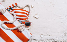 Beach Bag In White-red Stripes On The Sand, Sunglasses And A Swimsuit Stylized Under The American Flag Stick Out From The Bag. 4th Of July