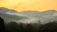 Wildfire Disaster Is Burning Forests On The Mountains. Emergency Services Helicopter Drops Water To Extinguish The Forest Fires That Burned The Forest On The Mountains.