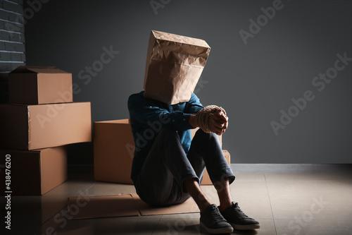 Male hostage with paper bag sitting on floor in room Fotobehang