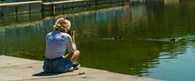 Mujer Sentada Al Lado De Un Lago Haciendo Fotos A Los Patos Con Su Cámara Réflex  , Mujer Joven Con Blusa Blanca Y Pantalones Cortos Azules Sujetando Una Cámara De Fotos