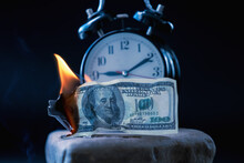Burning US Dollar Bills And The Clock As Symbol Of Lost Time And Opportunities. Selective Focus On Money. Horizontal Image.