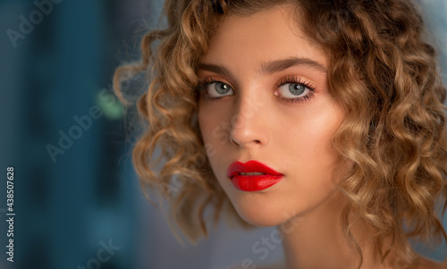 Obraz na plátně Portrait of Beautiful Fashion Model with Wavy Curly Hair and Colored Make-up with red Lips is posing front the Window