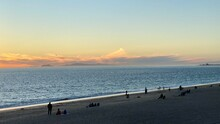 Silhouetted People On Beach At Point Mugu, California, With Sun Setting Over The Pacific Ocean. Catalina Island Visible On The Horizon