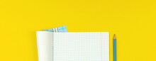 Education Banner With Opened School Notebook With Checkered Math Paper And Pencil On Yellow Table Background, Copy Space And Top View Photo