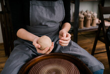 Person Softening Clay Mass Behind Pottery Wheel