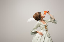 Stylish Woman In Retro Clothing Eating Delicious Pizza With Closed Eyes Isolated On Grey
