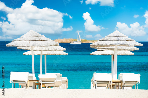 Murais de parede (Selective focus) Stunning view of some white thatch umbrellas and sunbeds on a white sand beach bathed by a beautiful, turquoise sea