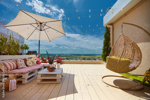 Canvas a cozy rooftop patio with wooden pallet furniture and hanging swing chair at sun