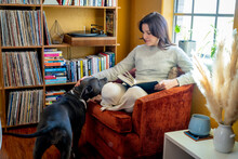 Woman Sitting In Chair With Book On Lap Petting Pitbull Dog