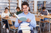 Portrait Of Young Man Smiling While Reading Interesting Book In Library