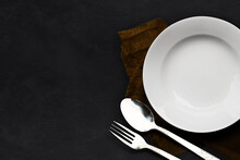 White Plate And Spoon, Fork Empty On Dark Stone Table Background