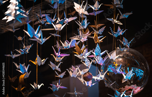 Fototapeta premium Lots of origami swans hanging from the roof, seen from underneath in a softly illuminated room