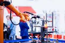Yellow Robot Hand Performs Welding Work On Metal Structures Industrial Automatic Factory, Light Background