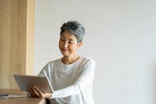 タブレットPCを見る日本人シニア女性