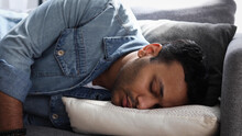 Exhausted Young Indian Man Sleeping On Couch At Home, Male Feels Tired And Sleepy After A Long Day At Work, Need Rest Concept