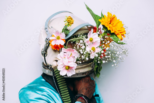 Obraz na plátně fine art concept with man wearing a space helmet and flowers composition