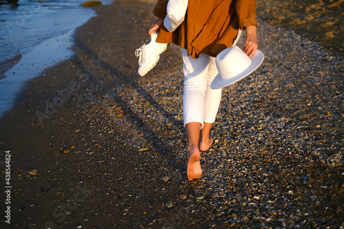 Stampa su Tela a girl in a white hat and light clothes walks along the embankment at the sea