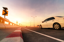 Motion Blur Of White Car Driving On Curve Concrete Road With Traffic Sign. Road Trip On Summer Vacation. Car Drive On The Street. Summer Travel By Car. Solar Panel Energy On Yellow Curve Traffic Sign