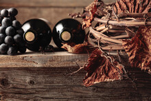 Bottles Of Red Wine With Grapes And Dried Vine On An Old Wooden Table.