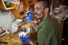 Joyful Young Man Making Glass Terrarium In Workshop