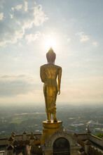 Aerial View Of Golden Buddha Pagoda Stupa. Wat Phrathat Khao Noi Temple Park, Nan, Thailand With Green Mountain Hills And Forest Trees. Thai Buddhist Temple Architecture. Tourist Attraction At Sunset.