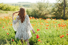Girl Wearing White Dress And Straw Hat Walks Among Red Poppy Flowers On The Sunset.