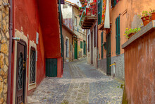 Beautiful Old Street In A Small Italian Town With Red Walls And A Green Door