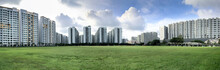 Panoramic View Of Apartment Buildings On Green Grass Field With Cloudy Sky, Singapore Public Housing Apartments In Punggol District, Singapore. Housing And Development Board (HDB)