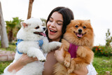Young woman hugging her two pomeranian spitz pups in the park. Couple of adorable red and white coated pom dogs outside on the walk. Close up, copy space for text, ocean background.