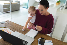 Caucasian Mother Holding Her Baby Taking Notes While Working From Home