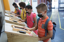 Group Of Diverse Students Wearing Face Masks Using Digital Tablets At School