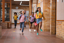 Group Of Diverse Students Running Together In The Corridor At School