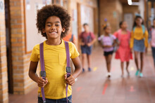 Portrait Of African American Boy Smiling While Standing In The Corridor At School