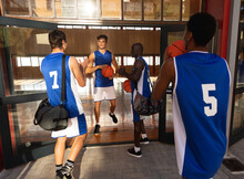 Diverse Male Basketball Team Holding Balls And Talking