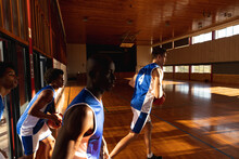 Diverse Male Basketball Team Holding Balls And Entering Gym