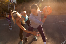 Diverse Female Basketball Team Wearing Sportswear And Practice Dribbling Ball
