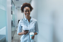 Portrait Of Mixed Race Businesswoman Smiling And Holding Smartphone