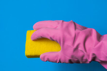 A Hand In A Pink Rubber Glove Holds A Yellow Sponge. Blue Background.
