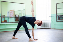 Young Man Practicing Classical Ballet In Black Clothing In Ballet Hall. Big Light Studio For Training Dancing.